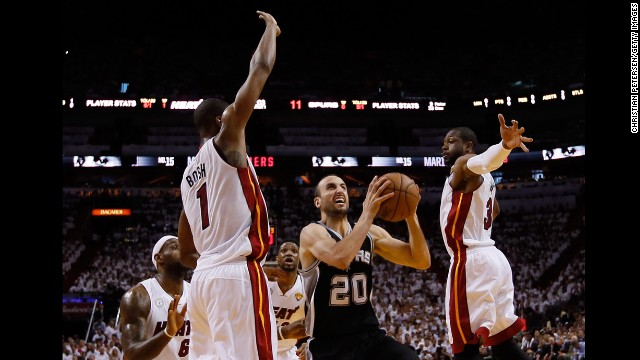 Manu Ginobili of the San Antonio Spurs goes up for a shot between Chris Bosh, left, and Dwyane Wade of the Miami Heat.
