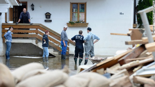 Residents stand in front of a house that was hit by floodwaters from the Danube River in Fischerdorf, Germany, on Tuesday, June 11.