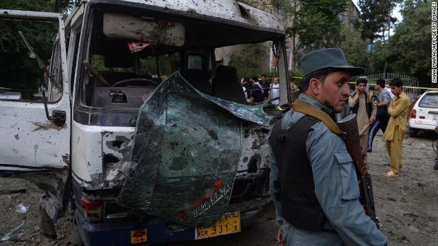An Afghan policeman stands guard in front of a badly damaged bus at the site of a suicide attack in Kabul on June 11, 2013. More than 1,000 Afghan civilians died in violent attacks in the first half of 2013, according to the U.N.