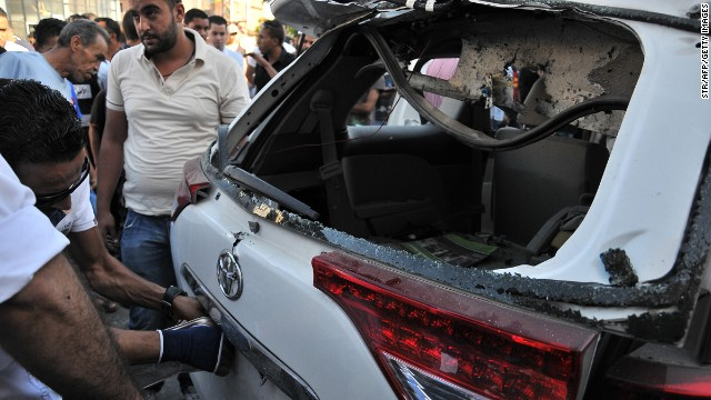 Libyan security forces examine the booby-trapped car belonging to Italian diplomats on Tuesday.