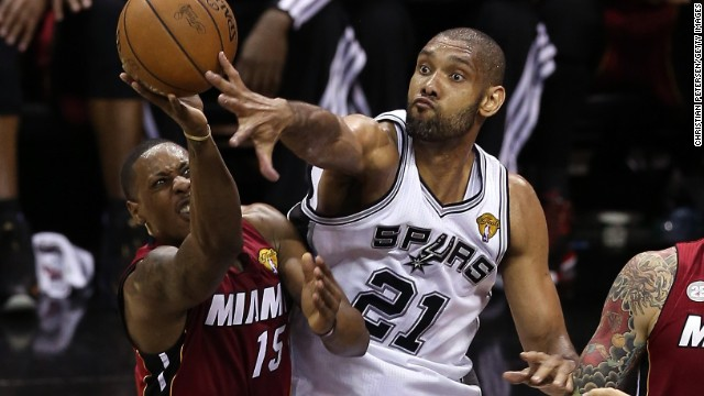 Mario Chalmers of the Miami Heat goes up for a shot against Tim Duncan of the San Antonio Spurs in the first half.