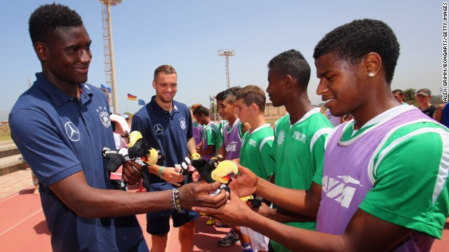 Striker Peniel Mlapa hands out small German mascots to some of the children at the Youth Village.