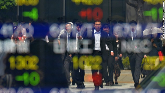 Pedestrians are reflected on a quotation board of the Tokyo Stock Exchanges in Tokyo. The benchmark Nikkei 225 index closed 6.4% down Thursday, losing 20% of its value since this year's high on May 22. Asia stocks followed suit.