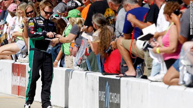 Jason Leffler signs autographs before a NASCAR race last year.