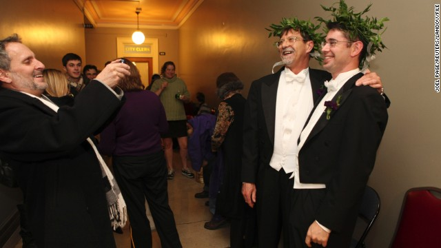 The second case before the Supreme Court is the Defense of Marriage Act, a 1996 federal law defining marriage as between a man and a woman. Here, Jamous Lizotte, right, and Steven Jones pose for photos while waiting for a marriage license in Portland, Maine, in December 2012.