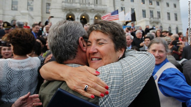Rhode Island state Sen. Donna Nesselbush, right, embraces a supporter after the Marriage Equality Act gets signed into law at the statehouse in Providence on May 2, 2013.