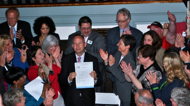 Delaware Gov. Jack Markell holds up legislation on May 7, 2013, allowing same-sex couples to wed.
