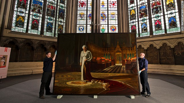 Momart employees hold a portrait of Queen Elizabeth II before it is moved into Westminster Abbey on May 17, 2013 in London.