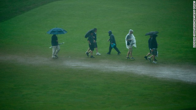 People traverse the 18th fairway during a weather delay on June 13.