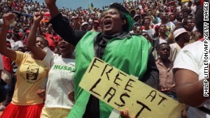 Jubilant residents of Soweto wait to hear newly freed Nelson Mandela speak at Orlando stadium February 12,1990. I\n