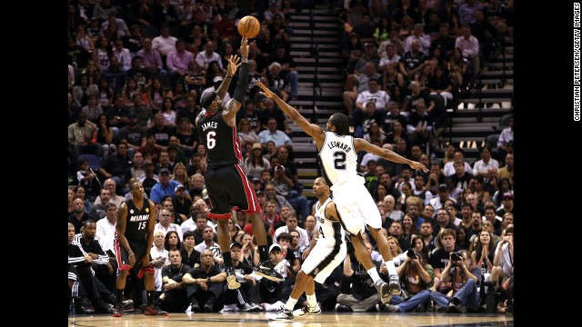 LeBron James of the Miami Heat takes a shot over Kawhi Leonard of the San Antonio Spurs.