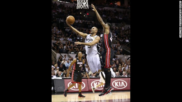 The Spurs' Tony Parker lays the ball up against Udonis Haslem of the Heat.