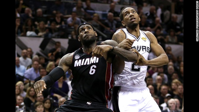 LeBron James boxes out Kawhi Leonard.