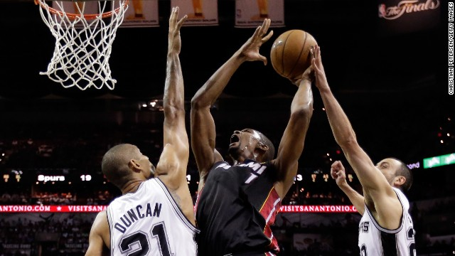 The Heat's Chris Bosh goes up for a shot against Tim Duncan, left, and Manu Ginobili.