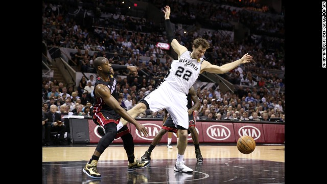 Tiago Splitter of the San Antonio Spurs loses his footing as Dwayne Wade goes for the ball.