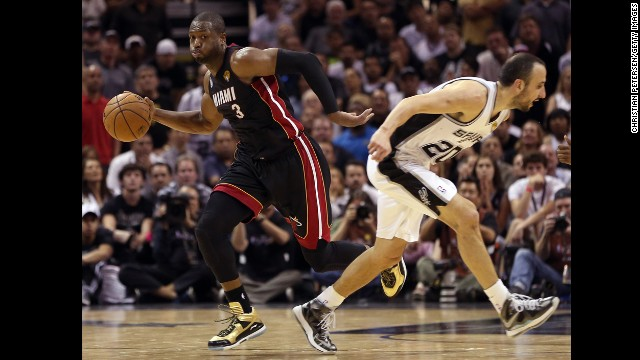 Dwayne Wade of the Miami Heat drives past Manu Ginobili in the fourth quarter.