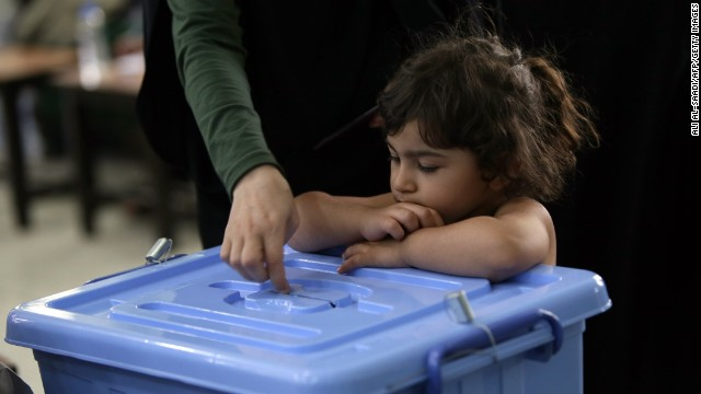A girl watches a woman cast her ballot on June 14.