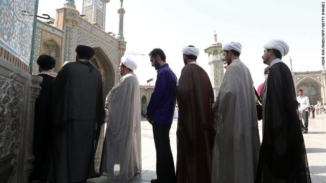 Iranian clergymen wait in line to vote at a polling station at the Massoumeh shrine on June 14.