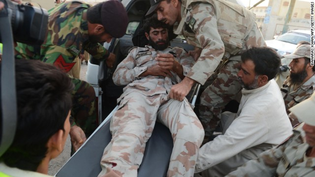 Soldiers shift an injured colleague into a van.