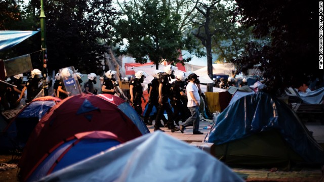 Riot police move in a line through the tent camp on June 15.