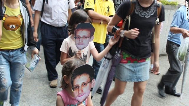 "Ruth Jopling brought her daughters, Amber, 8, and Jade, 3, to the protest, who held cut-out masks on sticks bearing Snowden's image. ""It's not just about our generation, but the next generation as well,"" Jopling said. Amber echoed her mother's sentiment: ""When I grow up, I can tell my children about this."""