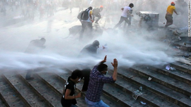 Protesters run for cover as riot police spray them with a water cannon on June 15.
