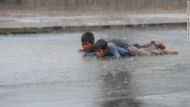Indian street children lie in a puddle along a road in New Delhi on Sunday, June 16. Click through to see other images of weather around the world.