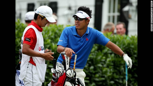 Hideki Matsuyama of Japan talks with caddie Daisuke Shindo on the first hole on June 16.