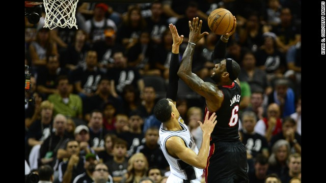 LeBron James of the Miami Heat shoots under pressure from Danny Green of the San Antonio Spurs during Game 5.