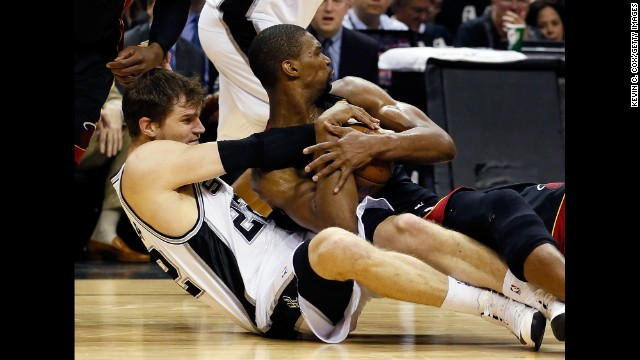 Chris Bosh of the Miami Heat and Tiago Splitter of the San Antonio Spurs wrestle for the ball.