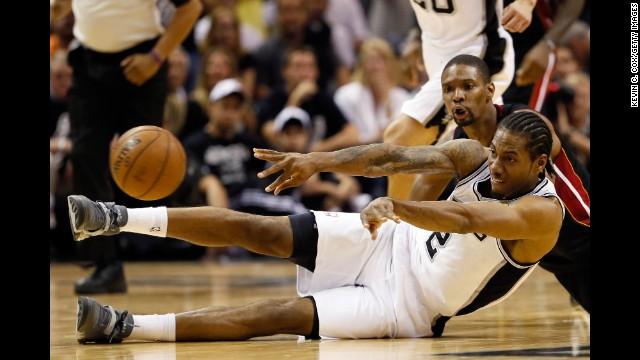 Kawhi Leonard of the San Antonio Spurs and Chris Bosh of the Miami Heat grapple over a loose ball.