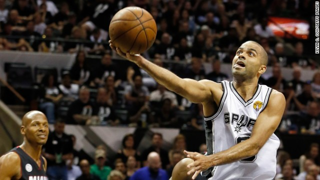 Tony Parker of the San Antonio Spurs goes up for a shot as Ray Allen of the Miami Heat looks on.