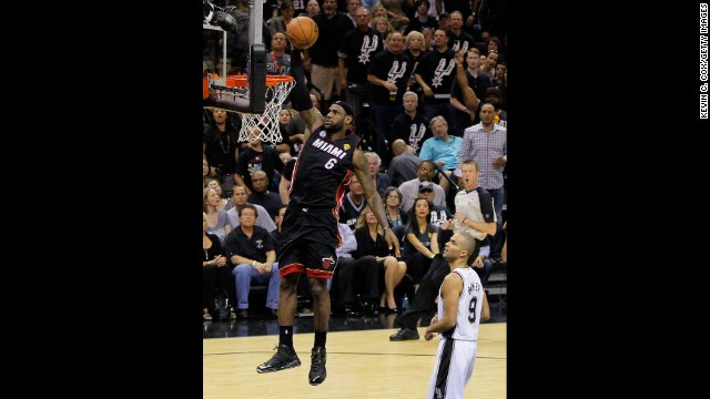 LeBron James of the Miami Heat dunks in front of Tony Parker of the San Antonio Spurs in the second quarter.