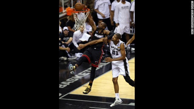Dwyane Wade goes up for a dunk over Tim Duncan of the San Antonio Spurs.