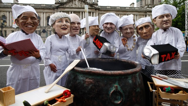 Oxfam charity volunteers wearing masks depicting the G8 leaders stand around a large cauldron outside City Hall in Belfast on June 16 to draw attention to the issue of world hunger.