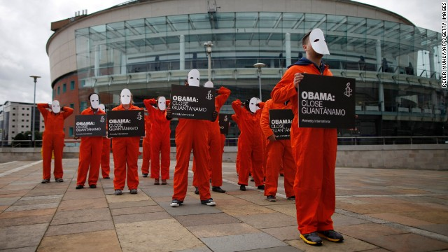 Amnesty International volunteers demonstrate outside the Waterfront Hall in Belfast on June 16 in masks and orange suits depicting detainees at Guantanamo Bay.