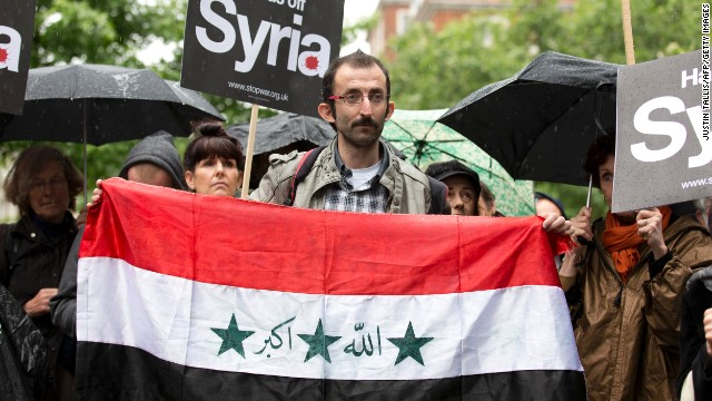 A man holds a Syrian flag outside the U.S. Embassy in London on Saturday, June 15, during a demonstration against Western involvement in the Syria conflict.