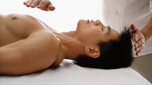 A man receives a reiki treatment. While alternative therapies can be valuable, some cross the line, according to Dr. Paul Offit.