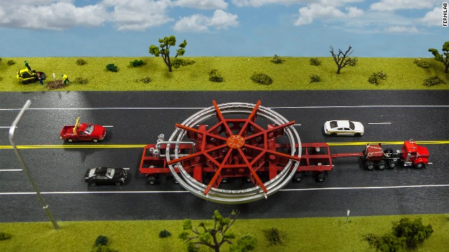 A model of the truck that will be used to transport the Muon g-2 ring, placed on a streetscape for scale. The truck will be escorted by police and other vehicles when it moves from Brookhaven National Laboratory in New York to a barge, and then from the barge to Fermi National Accelerator Laboratory in Illinois.