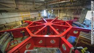 Crews work to attach the red stabilizing apparatus to the Muon g-2 rings at Brookhaven National Laboratory in New York in preparation for moving them over land and sea to Fermi National Accelerator Laboratory in Illinois.