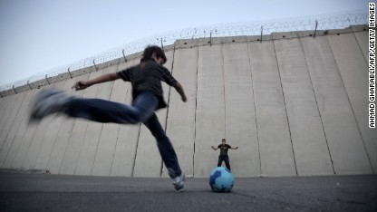 Palestinian children play football in front of the Israeli security fence in the West Bank village of Abu Dis, on the outskirts of Jerusalem.