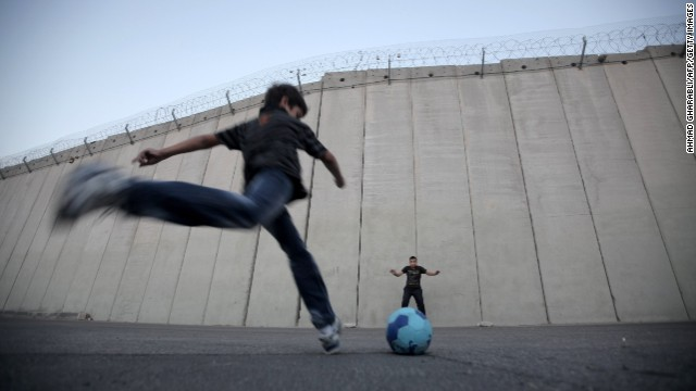 Palestinian children play football in front of the Israeli security fence in the West Bank village of Abu Dis, on the outskirts of Jerusalem. Organizations such as Mifalot help bring Palestinian and Israeli kids together through the power of football.
