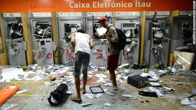 Two men look at smashed ATMs in Rio de Janeiro on June 17.