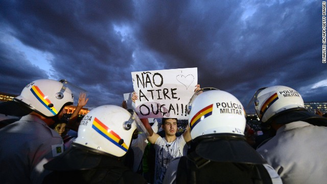 A student holds a sign reading 'Don't shoot, listen!!!' during a protest in the gardens of the National Congress, on June 17, 2013 in Brasilia.