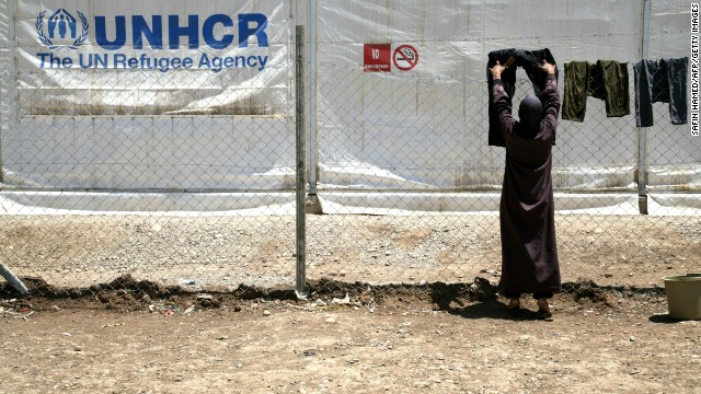 A woman uses a fence to dry laundry at the Domiz refugee camp near Kohuk, Iraq, in May 2013.