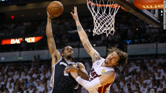 Kawhi Leonard of the San Antonio Spurs dunks on Mike Miller of the Miami Heat.