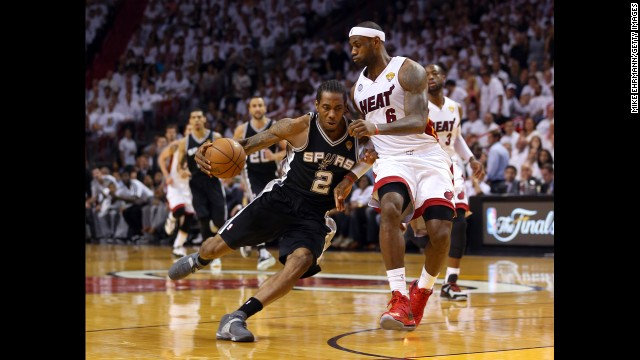 Kawhi Leonard of the San Antonio Spurs drives on LeBron James of the Miami Heat in the first quarter.