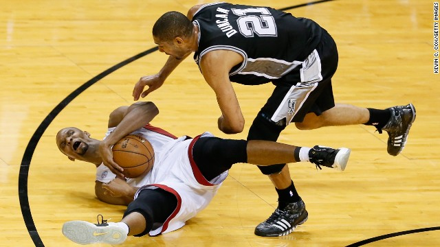 Chris Bosh of the Miami Heat falls with the ball as Tim Duncan of the San Antonio Spurs guards him.