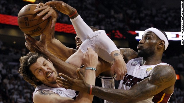 Mike Miller, left, and LeBron James of the Miami Heat vie for a rebound with Tim Duncan of the San Antonio Spurs.