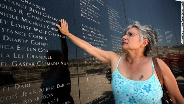 Joanne Festa touches the memorial wall commemorating the victims of TWA Flight 800 on July 16, 2006, at the Smith Point County Park in Shirley, New York.